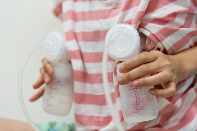 어머니는 자동 유방 펌핑 기계로 우유를 젖병에 펌핑하기 시작합니다. 모유는 신생아를 위한 최고의 건강 영양 식품입니다. 어머니와 아기 건강 관리 개념입니다.