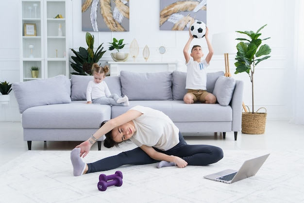 활동적인 정력적 인 아이들이 놀고있는 동안 어머니 스트레칭 운동. 요가하는 엄마