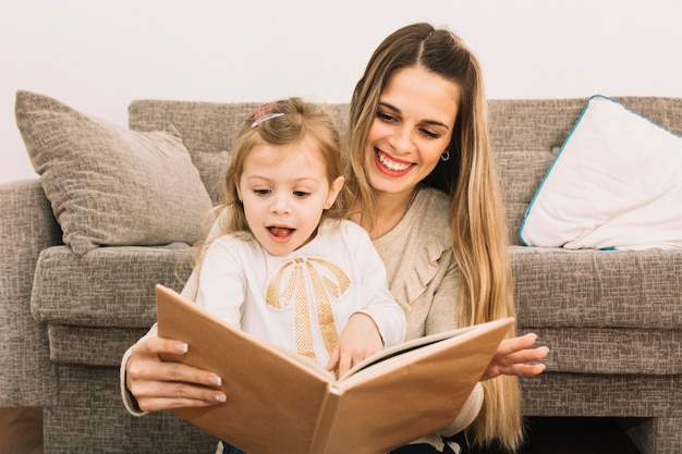 Mother and surprised daughter reading book near couch