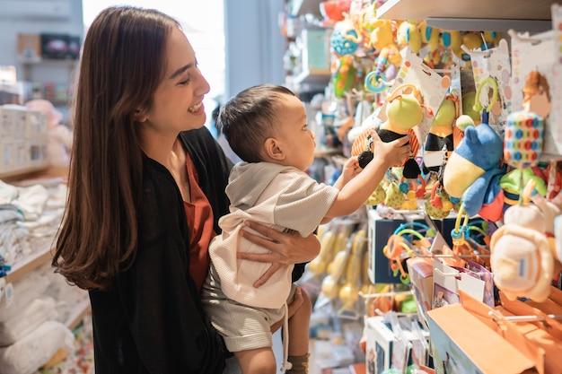 母はおもちゃを買うために彼女の歳の息子を連れて行きます