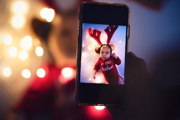 母親はスマートフォンで生まれたばかりの赤ちゃんの写真を撮ります。家族の思い出。