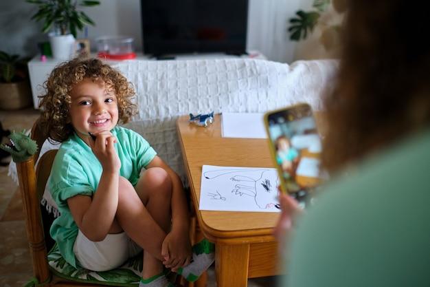 어머니는 마커 펜으로 종이에 그림을 그리는 아들의 스마트 폰으로 사진을 찍는다