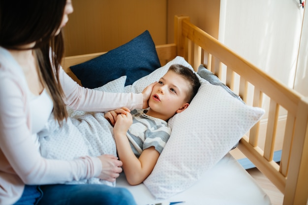 A mother takes care of her child who has a fever and fever. disease and healthcare.