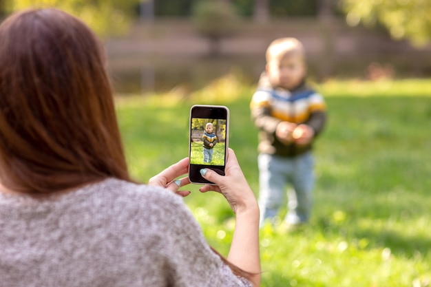 A mother takes pictures of her little son on a smartphone in a green park