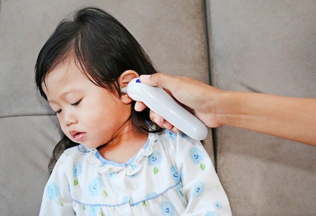 Mother takes temperature for her daughter with ear thermometer at home