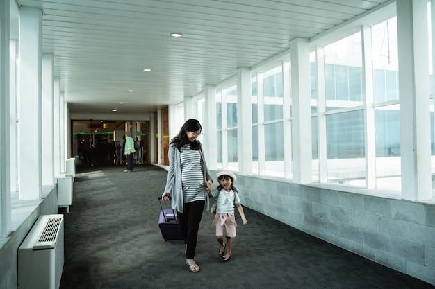 어머니는 비행기를 타기 위해 어린 소녀의 손을 잡는다
