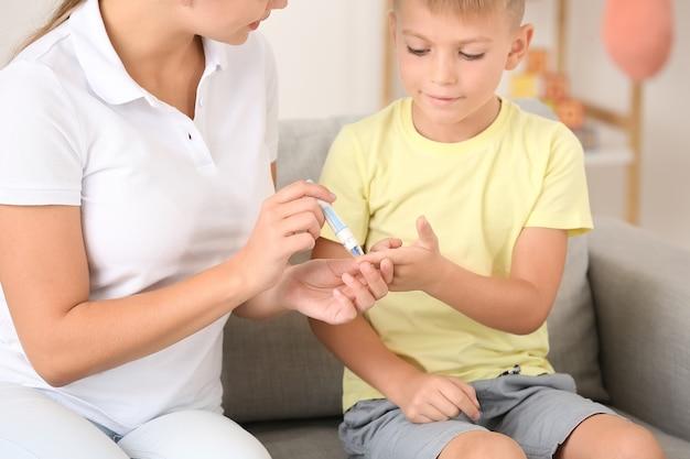 自宅で糖尿病の息子の血液サンプルを採取している母親