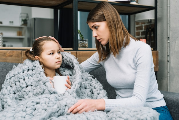 Mother taking care of her daughter covered with gray woolen scarf suffering from fever