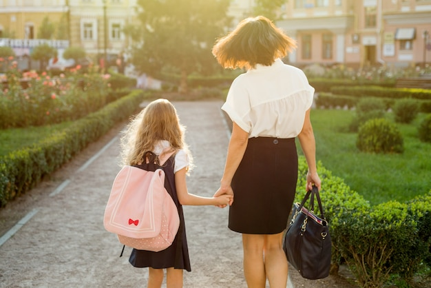 Mother taking daughter to school, back view.