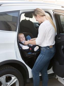 Мать вынимает ребенка из машины в сиденье безопасности