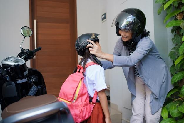 朝、バイクで娘を学校に連れて行く母親