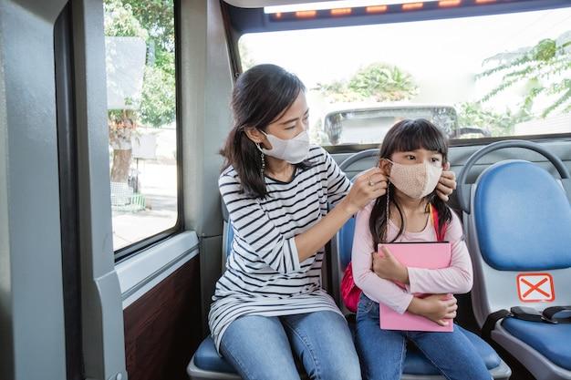 バスの公共交通機関のフェイスマスクに乗って娘を学校に連れて行く母親