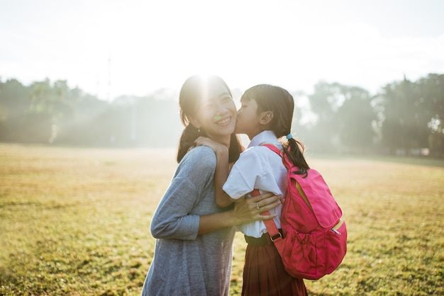 朝、娘を学校に連れて行く母親