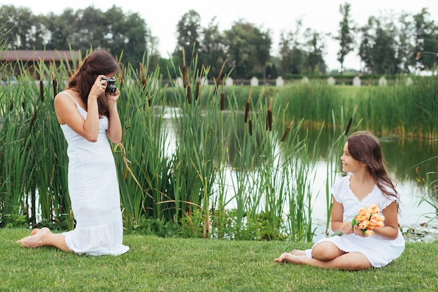 Mother taking photo of daughter by the lake