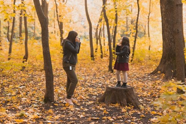 秋の公園の趣味やレジャーでレトロなカメラで彼女のカリスマ的な娘の写真を撮る母