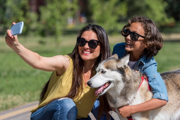 Mother taking selfie of son and dog at the park