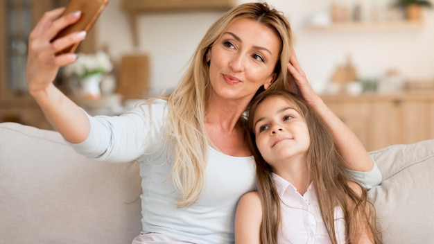 家で娘と一緒に自分撮りをしている母