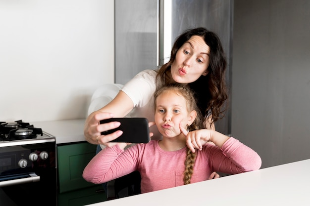 Mother taking selfie with daughter