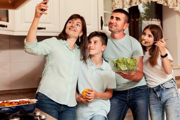 母は台所で家族と一緒にselfieを取る