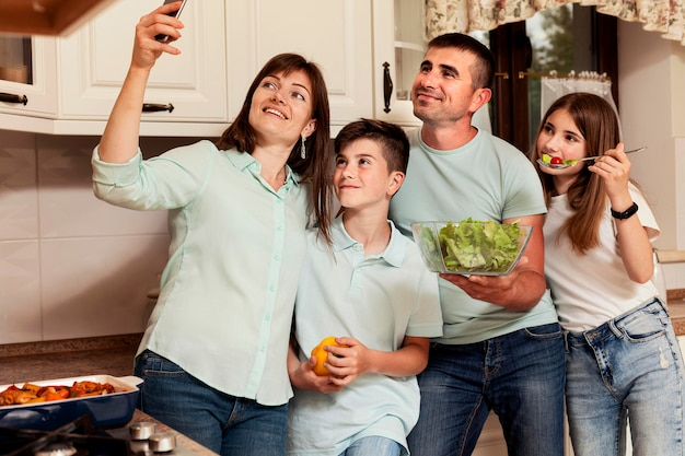 Mother taking selfie with family in the kitchen