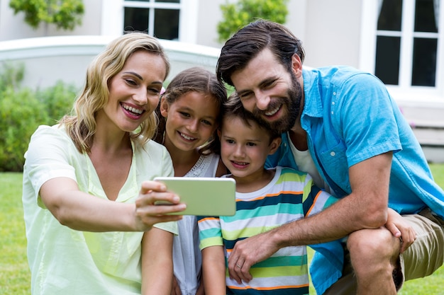 Mother taking selfie with family in yard