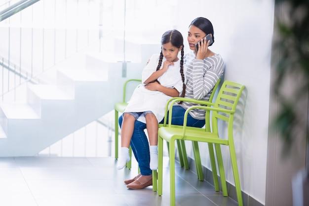 女の子が膝の上に座っている間携帯電話で話している母