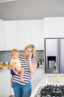 台所で彼女の女の赤ちゃんを保持しながら、母は携帯電話で話して