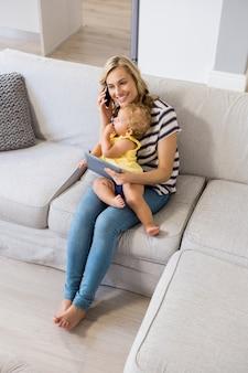 彼女の女の赤ちゃんを保持しながら、母は携帯電話で話して