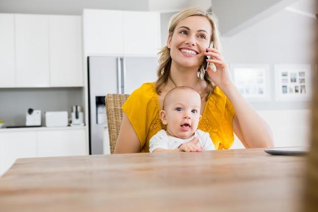 母は台所で赤ちゃんの男の子と携帯電話で話して