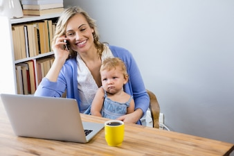 Mother talking on mobile phone with baby on her lap
