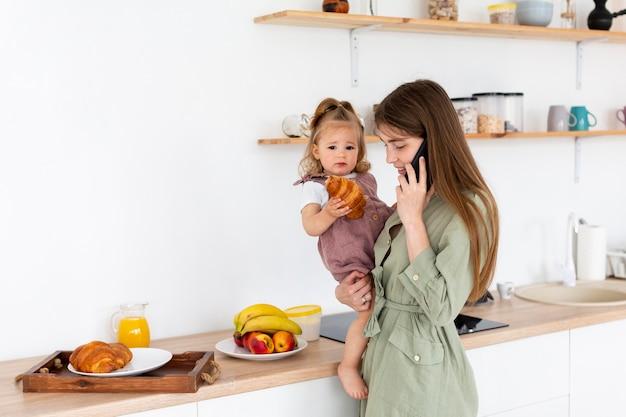 Мать разговаривает по телефону на кухне
