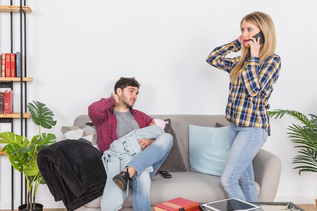 Mother talking on phone near father with baby