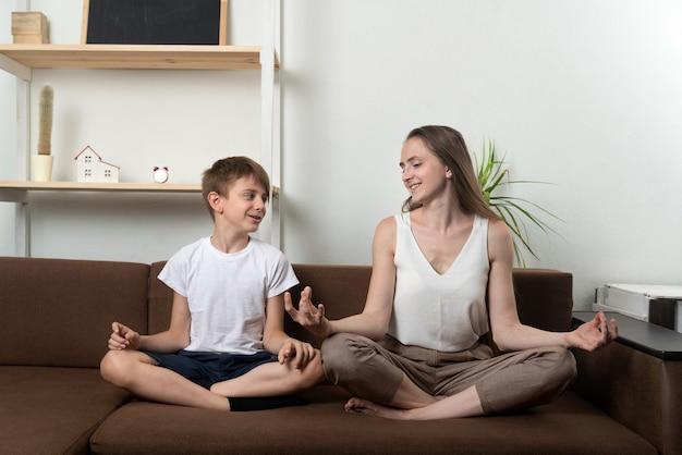 母は息子にソファに座って瞑想するように教えます。子供と一緒に家でヨガ。