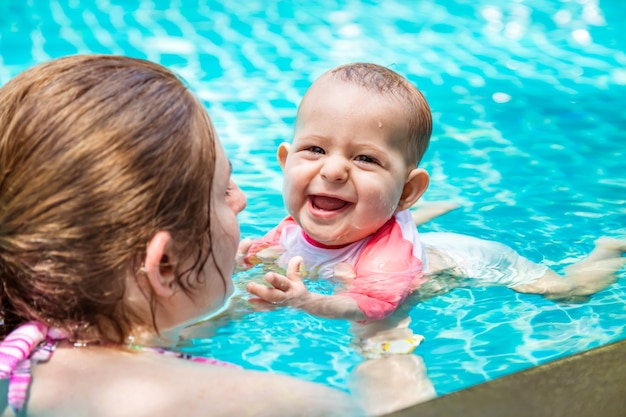 母は赤ん坊の娘に8ヶ月の夏休みを幼児と一緒に泳ぐように教えます幸せな笑いの子供たち
