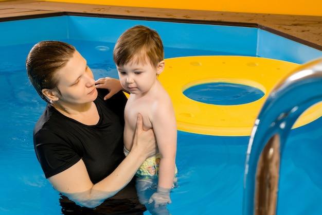 Мать учит ребенка плавать в закрытом бассейне