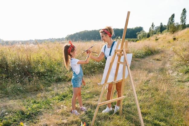母は公園で娘の絵の具を教えています。日当たりの良い自然、ママと娘は公園で絵を描き、小さな子供、子供の創造性を描きます。