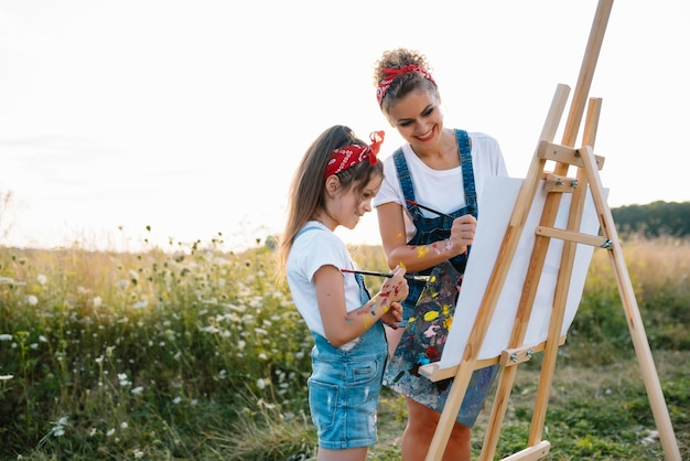 Mother teaches daughter paint in park. sunny nature, mom and daughter paint a picture in a park , painting a little child, child creativity.