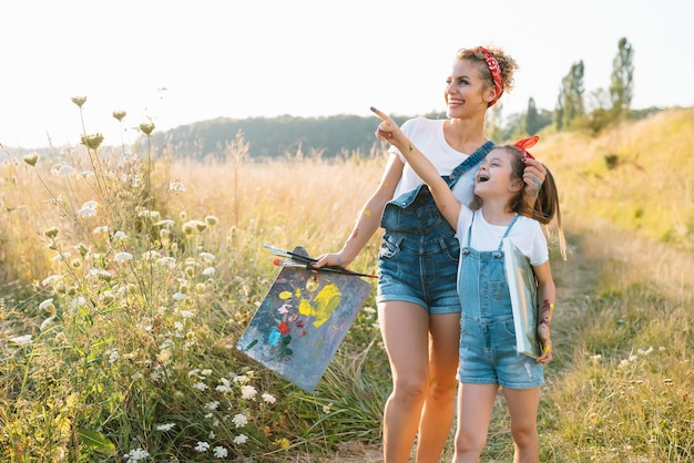 Mother teaches daughter paint in park