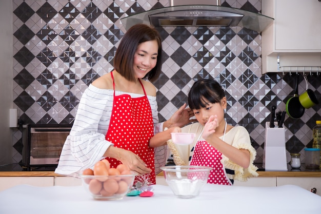Mother teaches daughter prepare dough in the kitchen.concept family happy.