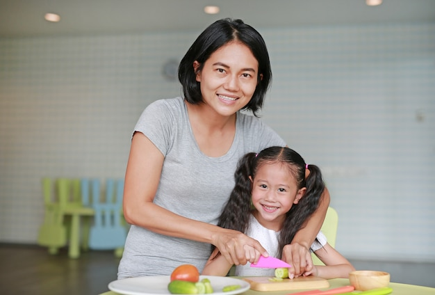 Mother teaches her children to cooking. close up asian mom and daughter slicing cucumber vegetable on chopping board at play room.