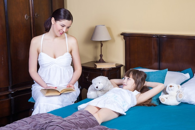 Mother teaches her daughter to read relationships between parents and children education comfortable