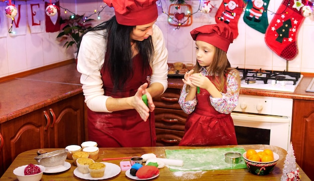 Mother teaches her daughter to work with sugar mastic for decorete cupcakes. preparing a christmas decorations for cupcake.