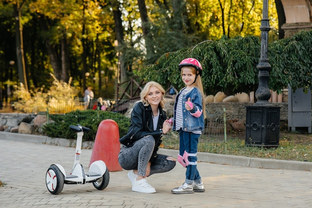 A mother teaches her little daughter to ride a segway in the park during sunset.