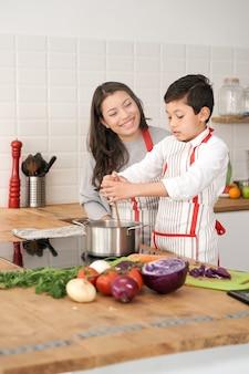 어머니는 부엌에서 건강한 음식을 요리하는 방법을 아들에게 가르칩니다. 라틴 사람들과의 라이프 스타일. 요리를 배우는 아이.