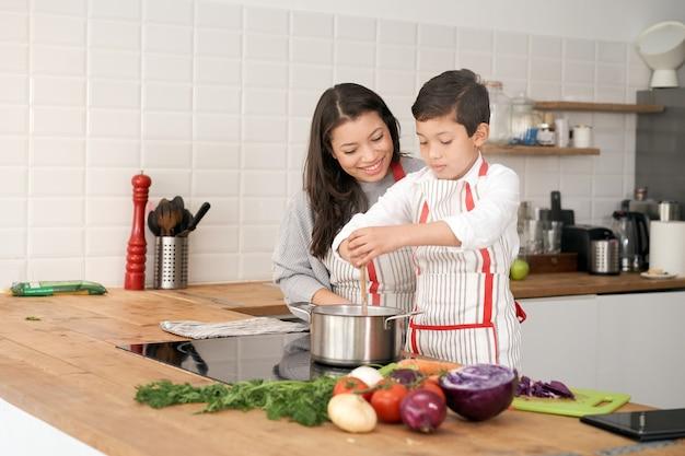 어머니는 라틴계 아이와 함께 부엌 생활 방식에서 약간의 야채를 요리하도록 아들을 가르칩니다.
