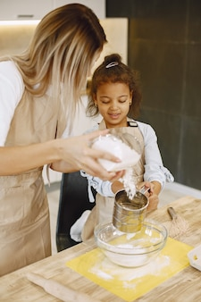Mother teaching afro-american daughter to make cookies at kitchen counter. kitchen is light.
