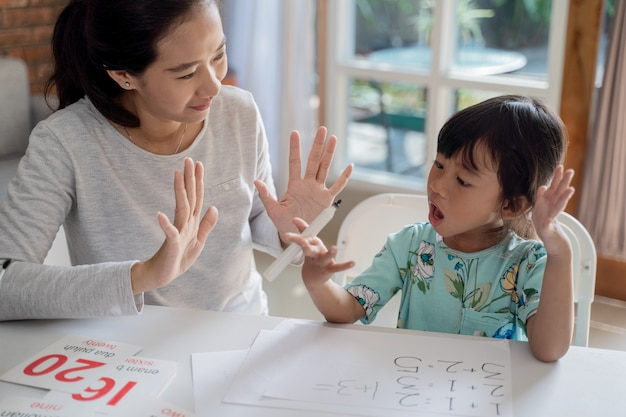 Mother teaching basic maths to her little daughter