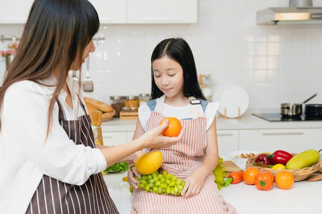Mother teaching child to eating fruit and advise to eat orange for vitamin c and healthy food.