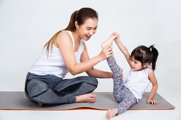 Mother teaching cute daughter to stretching leg muscles.