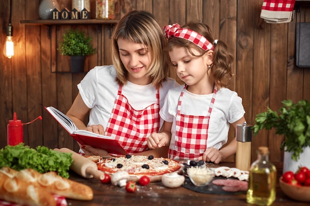 Mother teaching daughter cooking pizza